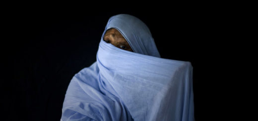 Bushra Shari, 39, adjusts her veil as she poses for a photograph in Lahore, Pakistan, Friday, July. 11, 2008. Bushra was burnt with acid thrown by her husband as she was trying to get divorced from him five years ago. She has undergone plastic surgery 25 times to try to recover from her scars. (AP Photo/Emilio Morenatti)