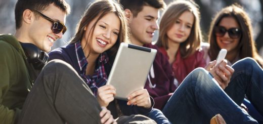 Young and happy teenagers using digital tablet and smart phone outdoors.